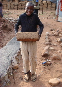 Limpopo - Ka-Mingha, young boy carrying mud brick for laying