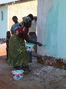 Malawi - Lilongwe Area 49, woman painting the wall of her house2